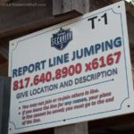 Sign stating to report line jumpers at Six Flags over Texas
